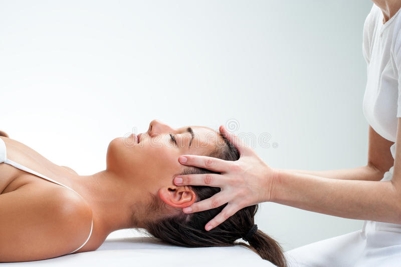 Therapist doing healing osteopathic treatment on woman. Close up of chiropractor doing healing osteopathic treatment on woman. Hands on head royalty free stock photos