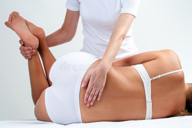 Therapist doing lower back massage on woman. stock photo