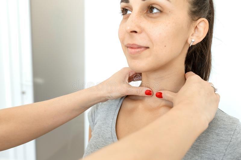 Therapist examines a young girl patient. Throat in neck, thyroid enlargement stock images