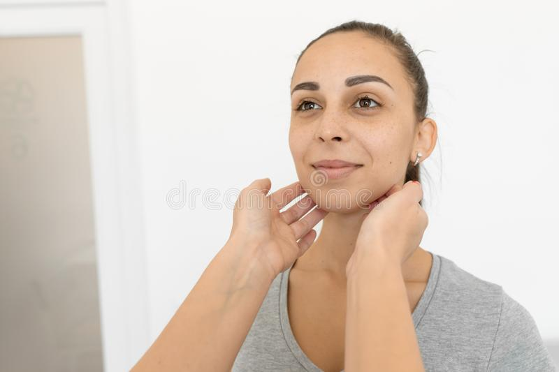 Therapist examines a young girl patient. Throat in neck, thyroid enlargement.  royalty free stock image