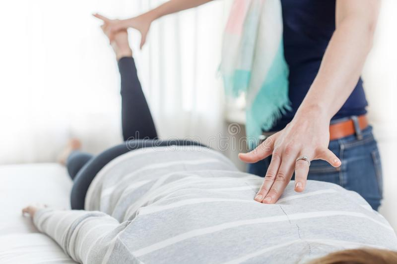 Therapist giving Kinesiology treatment in bright room. Therapist giving Kinesiology treatment in bright white room. Massage treatment being given royalty free stock image