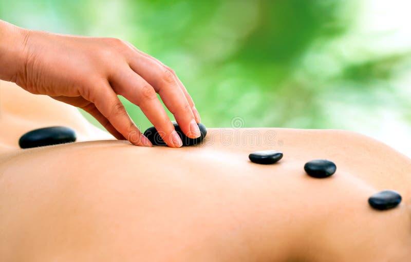 Therapist hand doing hot stone massage. royalty free stock image