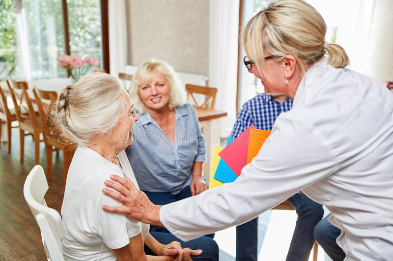 Therapist looks after seniors in group therapy. Psychotherapist looks after seniors in a group therapy session royalty free stock images