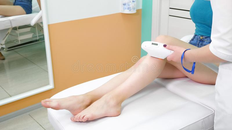 Therapist makes laser hair removal on visitor leg close view stock photography
