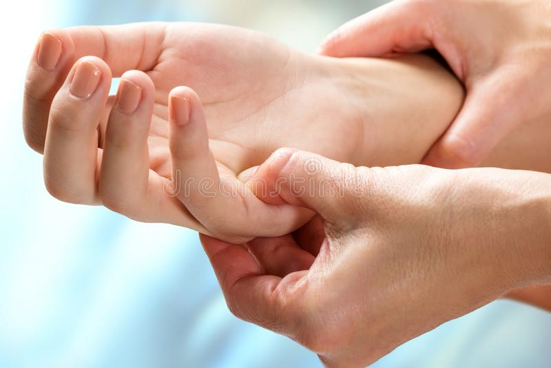 Therapist manipulating sensitive area on hand. Macro close up of kinesiologist manipulating sensitive area on female hand stock images