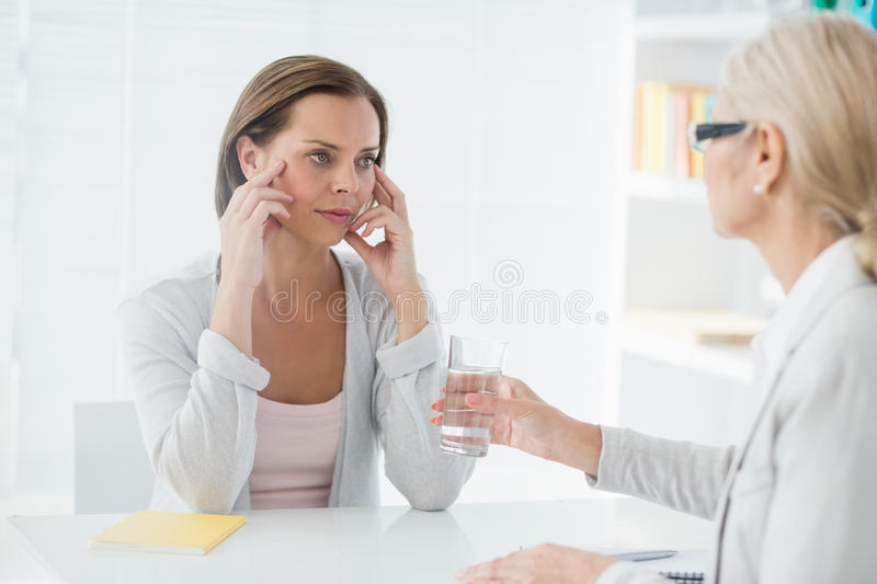 Therapist offering glass of water to her patient stock images