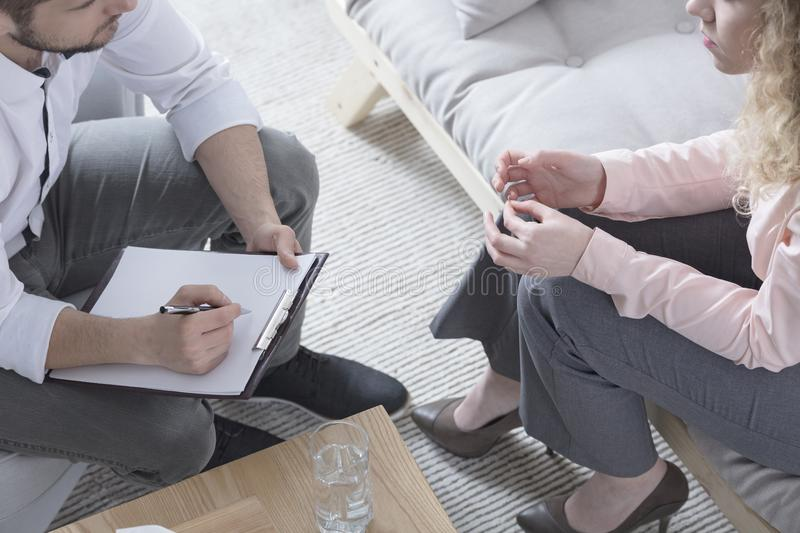 Therapist with paper and pen. Therapist sitting in front of patient with paper and pen stock image