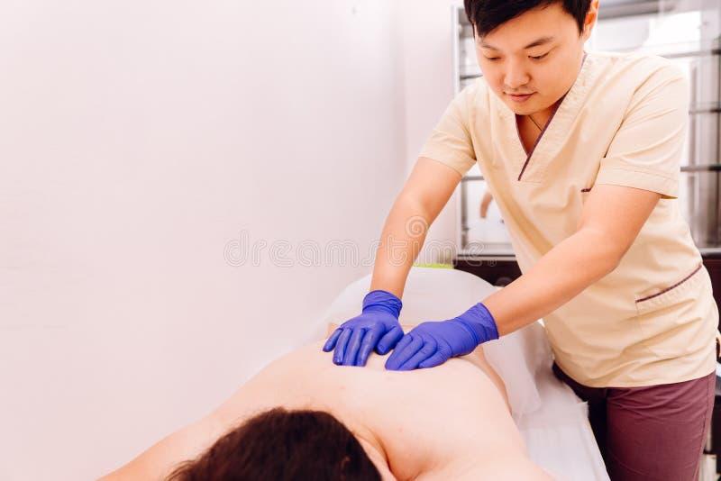 Therapist performing Gua Sha massage on woman stock photography