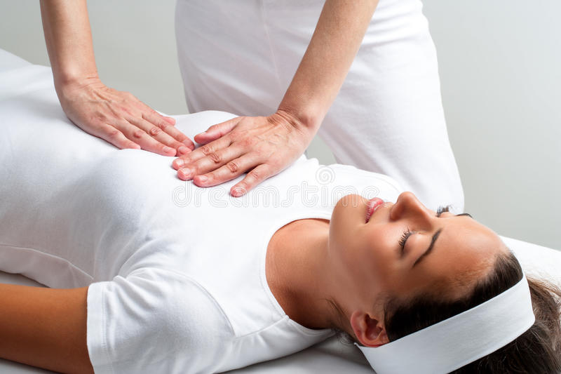 Therapist pressing with hands on womans chest at reiki session. stock images