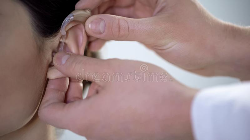 Therapist putting on deaf aid on young lady ear, disabled rehabilitation care stock photo