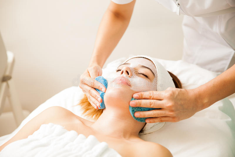Therapist removing a cream mask at the spa stock images