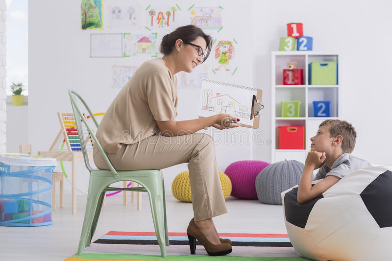 Therapist showing drawing to boy. Young therapist in high heels showing drawing of house to boy in classroom stock photography