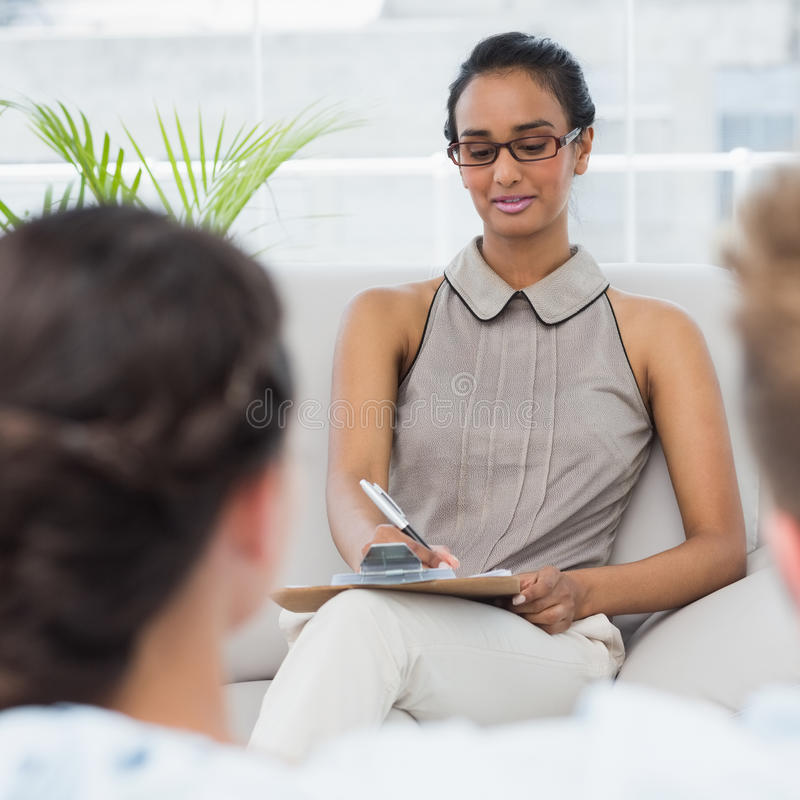 Therapist talking with couple on the couch and taking notes. In therapists office stock photos