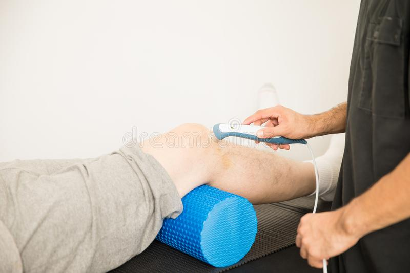 Therapist Using Ultrasound To Treat Patient`s Knee In Hospital. Cropped image of therapist using ultrasound probe to treat patient`s knee in hospital royalty free stock photo