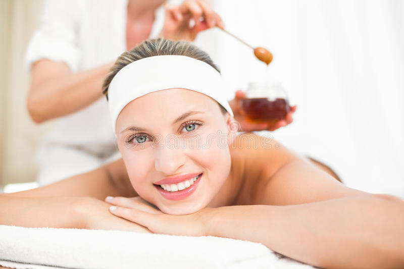 Therapist waxing womans back at spa center royalty free stock photography