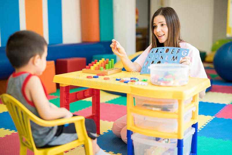 Therapist working with a little kid. Cute Hispanic language therapist working with a kid in a special needs school stock photo