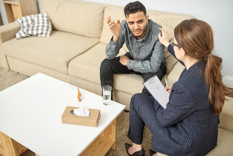 Therapy Session with Depressed Patient. Handsome young men suffering from depression sitting on sofa while having therapy session with highly professional royalty free stock images