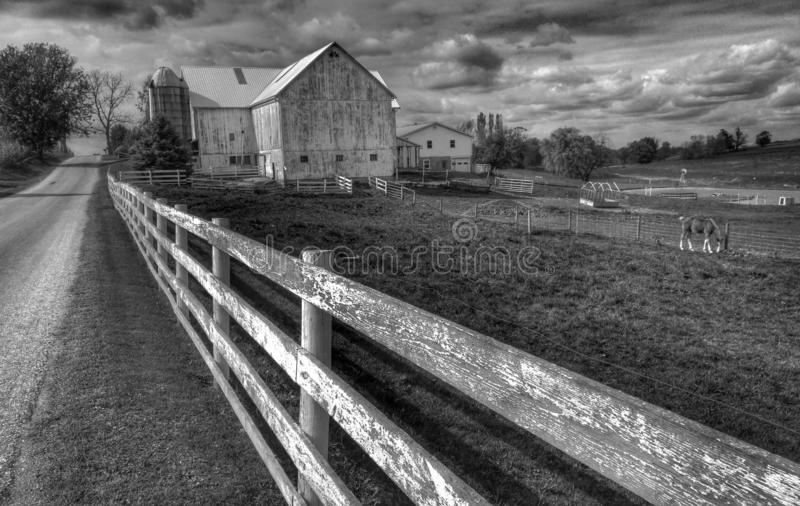 A pretty black & white scene of a horse, white fence, and a wooden farm in Ohio`s Amish Country - OHIO - AMISH - USA. There's more to be seen than scenery royalty free stock photo