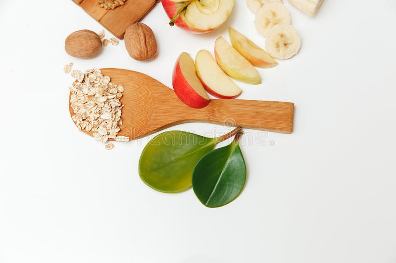 There are Banana,Aple,Orange with Walnuts in the Wooden Plate and Rolled Oats,Wooden Spoon,Trivet,with Green Leaves,Healthy Fresh. Organic Food on the White royalty free stock photography