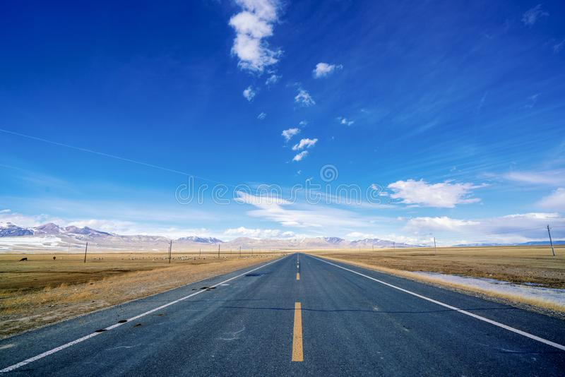 Endless straight road to snow mountains on plain with blue sky and white clouds. There is an endless straight road on plain to far away under blue sky and white stock photo