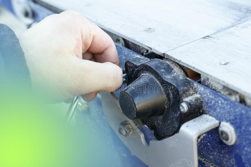 there is a flare. machine for cutting wood. master unscrews the bolt by hand royalty free stock photo