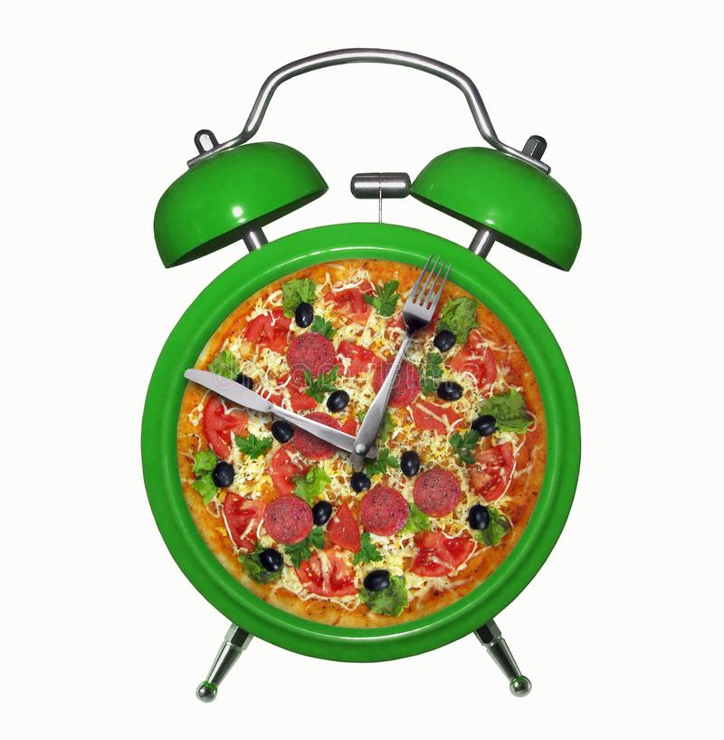 Green alarm clock with pizza stock photography