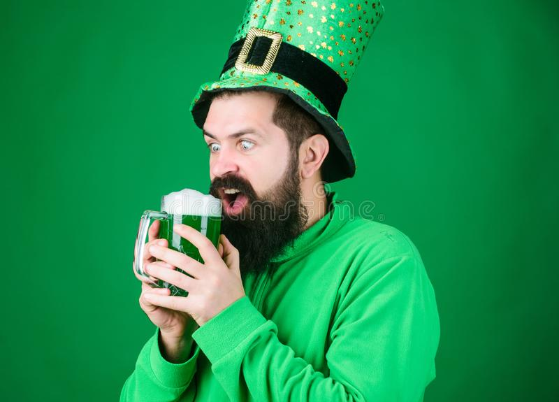 There are many good reasons for drinking. Irish man with beard drinking green beer. Celebrating saint patricks day. Hipster in leprechaun hat holding beer mug royalty free stock image