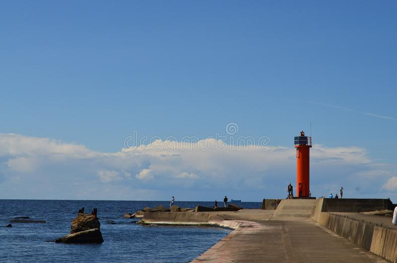 There is no end of road. Lighthouse, pier, sky, horizon, nature, water, ocean, red, landscape, wallpaper, peace, europe, beautiful royalty free stock images
