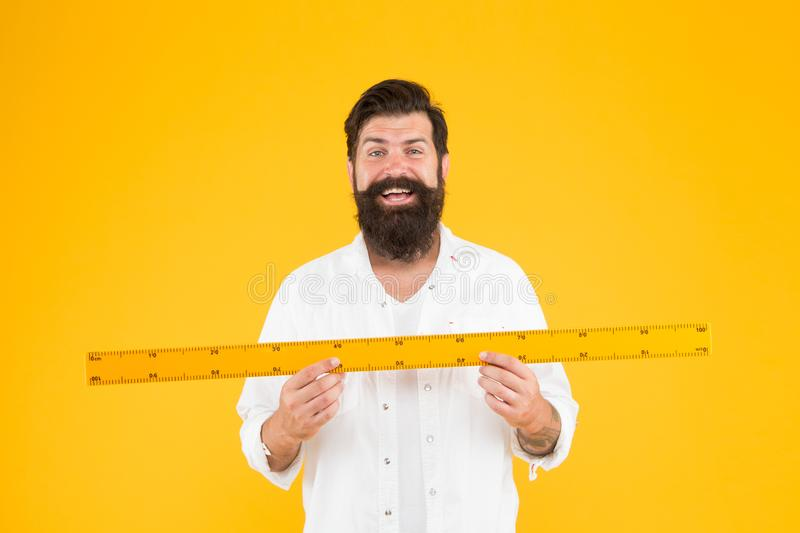 There is no substitute for a great teacher. Happy teacher holding ruler on yellow background. Maths teacher smiling with royalty free stock photography