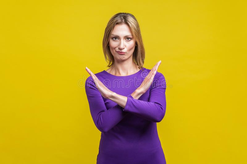 There is no way. Portrait of woman crossing hands, showing block, X sign, this is the end. indoor studio shot  on yellow. There is no way. Portrait of woman in royalty free stock photos