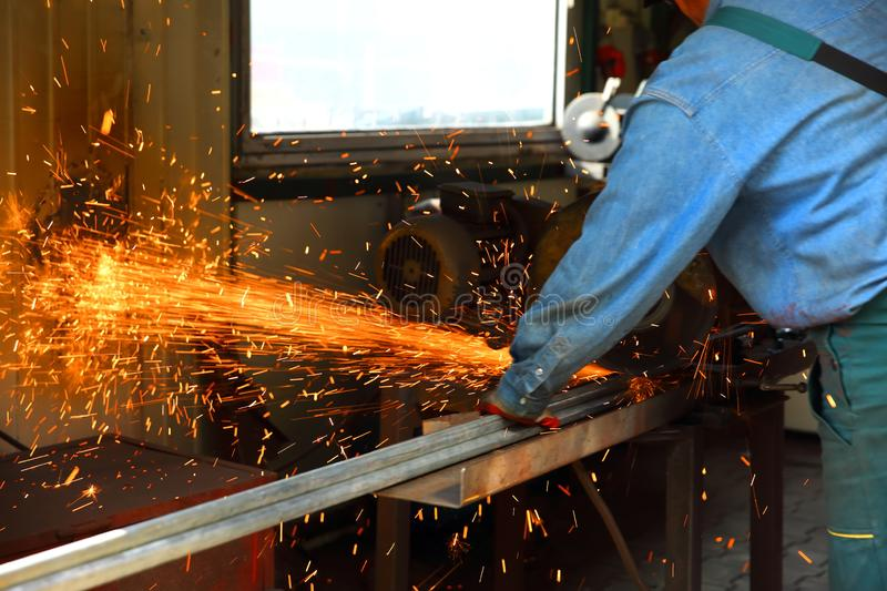 Cutting steel with a stationary grinder. stock photos