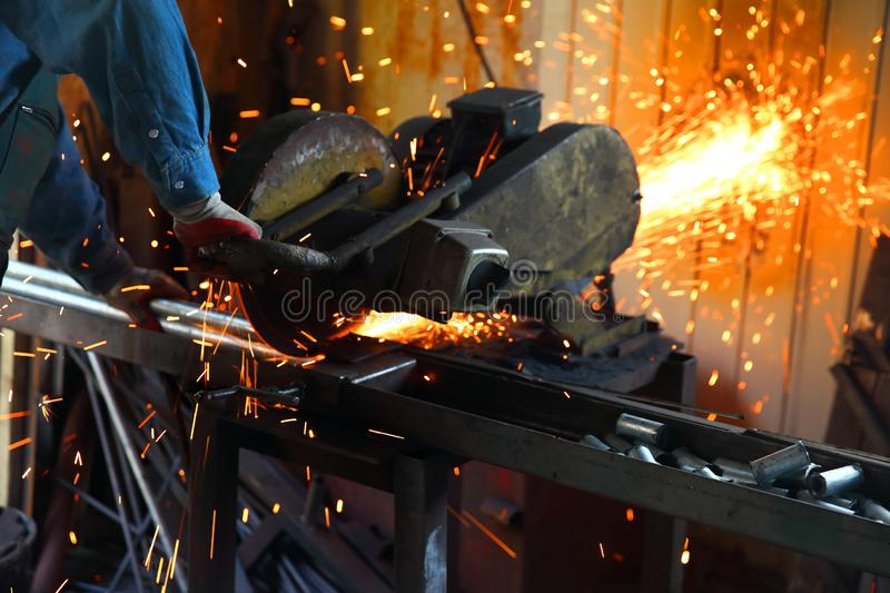 Cutting steel with a stationary grinder. stock image