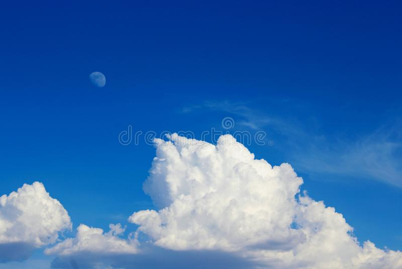Beautiful white clouds and the moon in the sky, Death Valley National Park. There are pure and beautiful white clouds and the pale moon in the clear blue sky of royalty free stock image