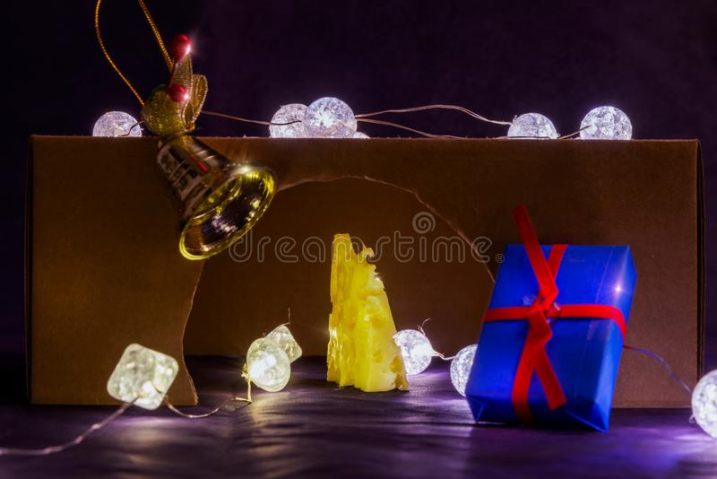 There is rat hole and gold cheese. There are glowing lights inside and on the rat hole. There are blue gift and gold bell. royalty free stock photos
