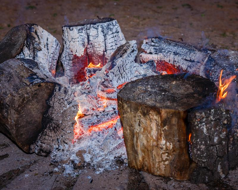 Red coal and fire flames in the middle of the campfire. There are red coal and fire flames in the middle of the campfire, but there are big, burning ash blocks stock images