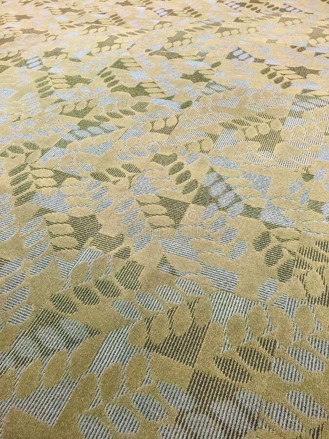 Contemporary textured gold, white and green  carpeting. stock images