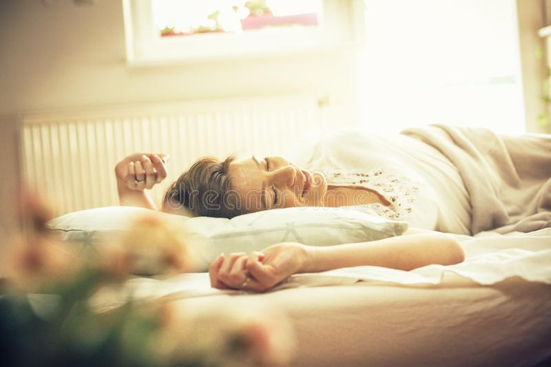 There`s nothing as good as a day off. Young woman waking up in bed. Space for copy royalty free stock photo