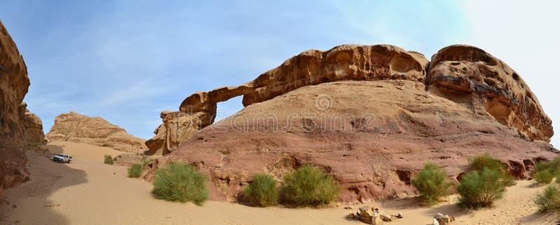 Vehicle dwarfed by the rock bridge at Jebel Burdah , Wadi Rum, Jordan royalty free stock photography