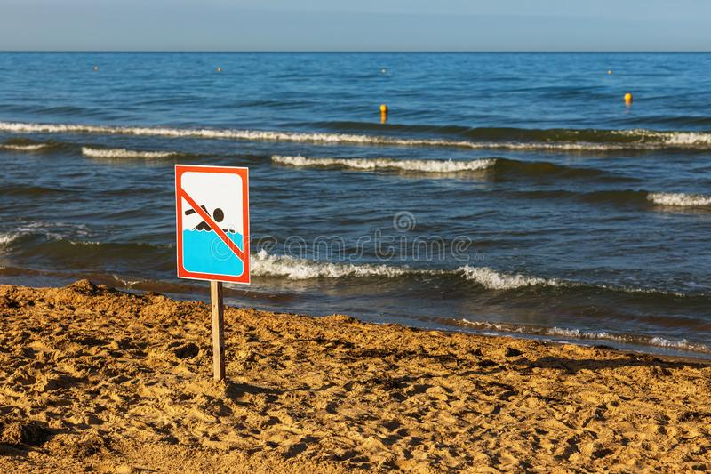 There is a sign on the beach prohibiting swimming due to the storm. There is sign on the beach prohibiting swimming due to the storm stock photo
