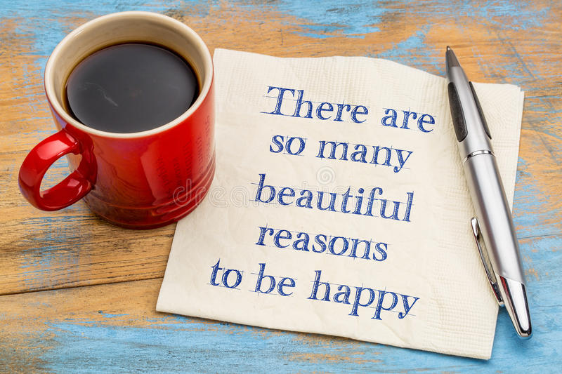 There are some many beautiful reasons to be happy. Handwriting on a napkin with a cup of coffee stock photo