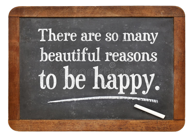 There are some many beautiful reasons to be happy. White chalk text on a vintage slate blackboard stock photo