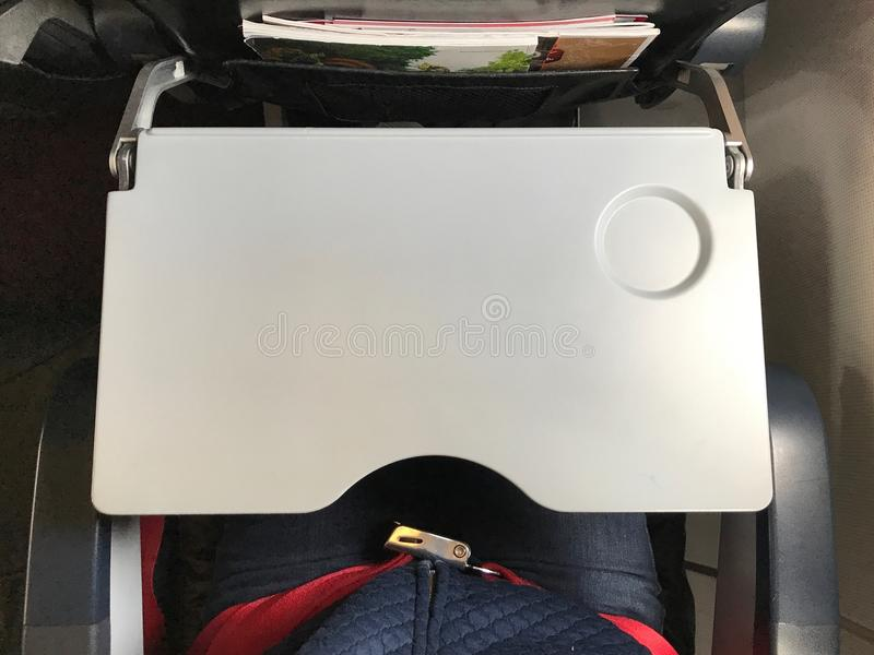There are tray table and seat belt for passenger in each chair on the plane. stock photography