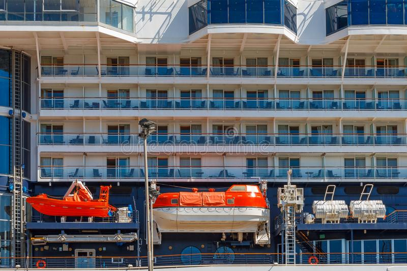 There are two orange lifeboats on the board of cruise ship. A eight floors cruise liner with orange lifeboats is in the port in. There are four orange lifeboats royalty free stock images