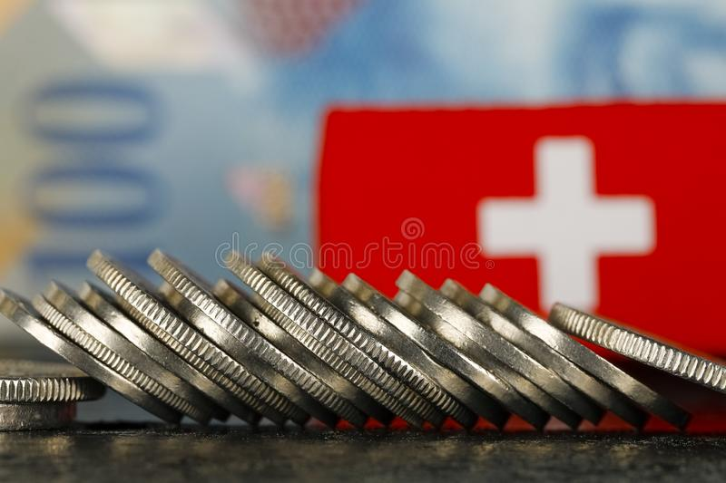 Swiss Money and Flag. There are various Swiss coins visible against background of one hundred francs banknote and there is Swiss flag as well stock images