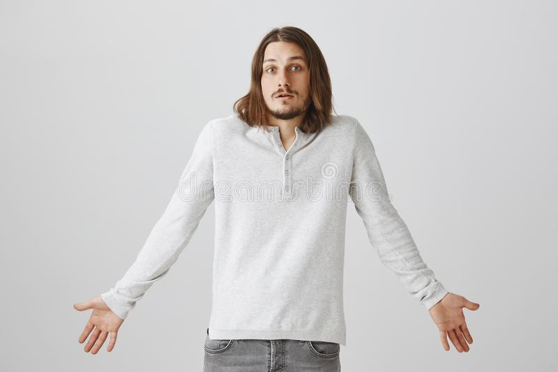 There was nothing I could do to help. Portrait of confused puzzled european male with beard and long hair standing in. White pullover, spreading hands and royalty free stock images