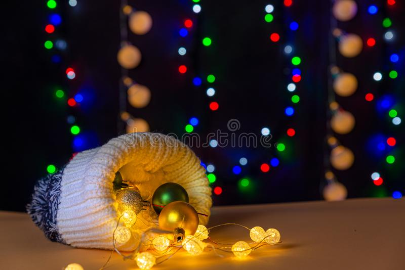 There are winter hat and glowing lights and different colors balls inside the hat are on the table/background. There are the different colors on the background stock photos