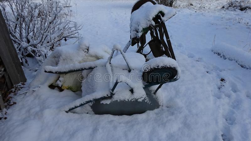 Winter. Snowy wheelbarrow and old chainsaw. royalty free stock image