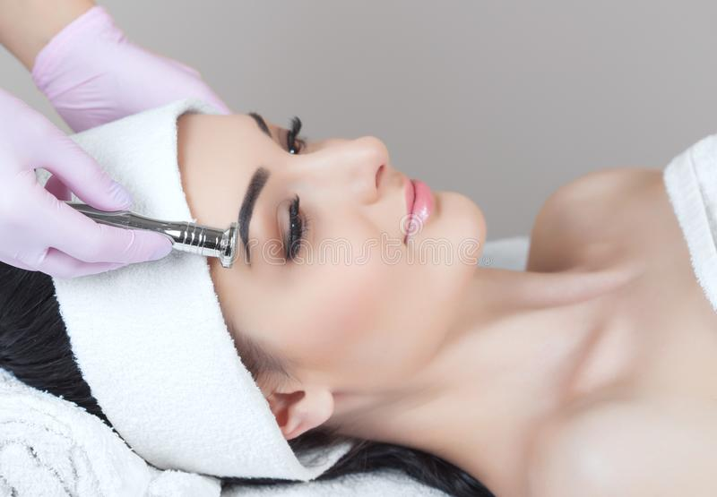 There is a woman, who is making the procedure Microdermabrasion of the facial skin in a beauty salon stock image