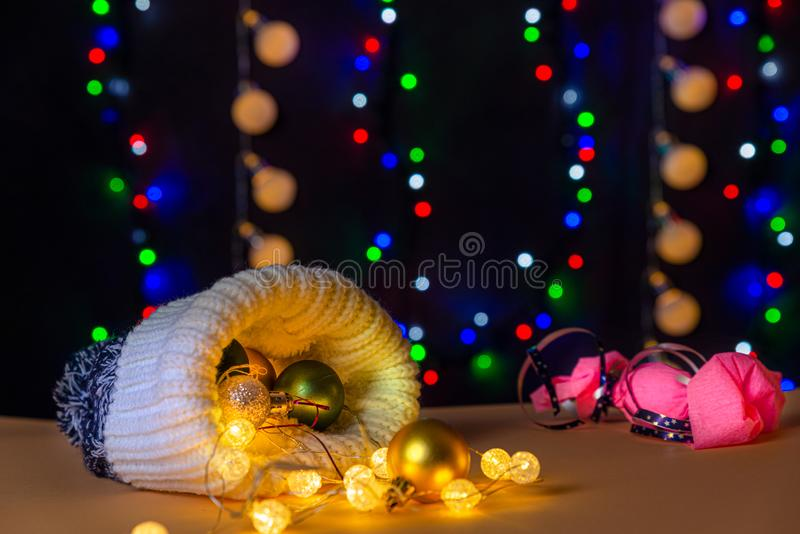 There are wool hat, different colors balls and lights on the table/background. There are pink candy and different colors lights. There are wool hat, different royalty free stock image