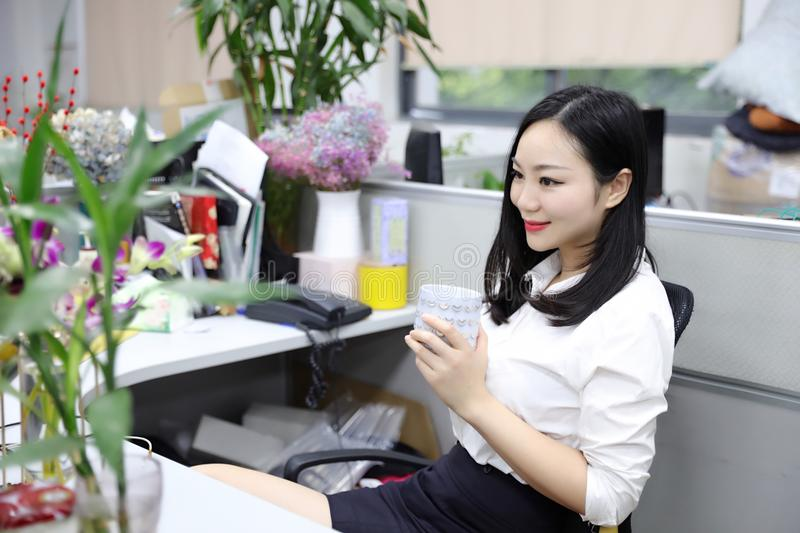 Asia Chinese office lady woman girl on chair thinking drink tea work laptop computer smile wear business occupation suit workplace royalty free stock images